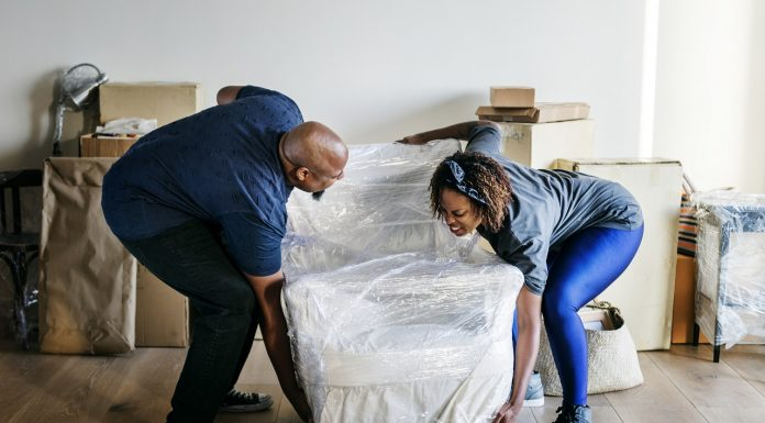 couple moving their furniture into a new house
